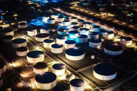 Aerial view oil refinery storage tanks illuminated at night Los Angeles USA