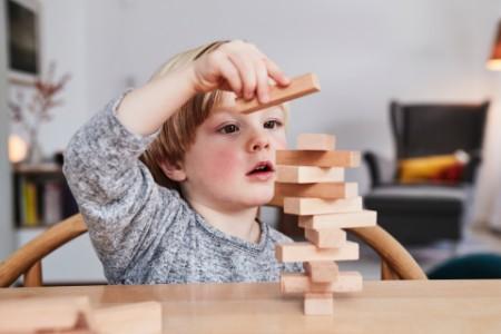 Boy building structure wooden building blocks