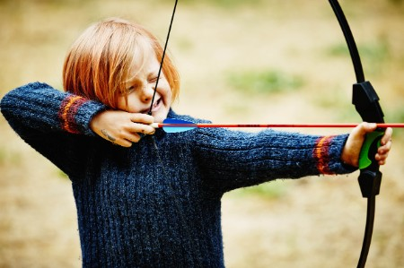boy learning to use bow and arrow