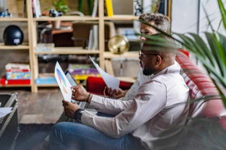 Businessmen laptop documents sofa loft office