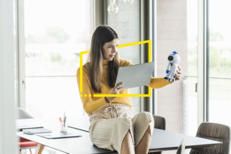 businesswoman holding robot and tablet