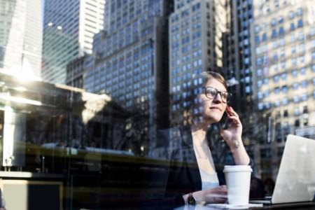 Businesswoman phone through window reflection