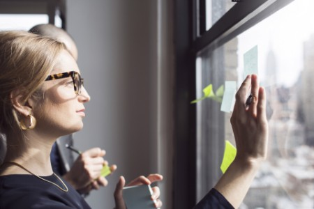 Business woman sticking notes on glass window
