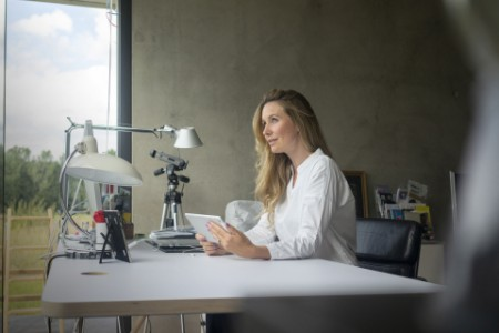 Businesswoman wokring at desk at home