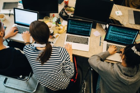 Computer programmers coding on laptops at desk in small office