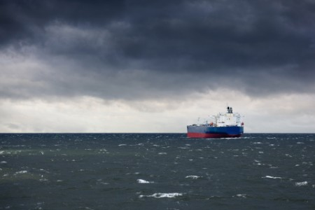 Container ship sailing towards dark storm clouds