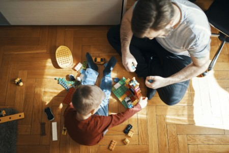 Father son sitting floor playing together building bricks