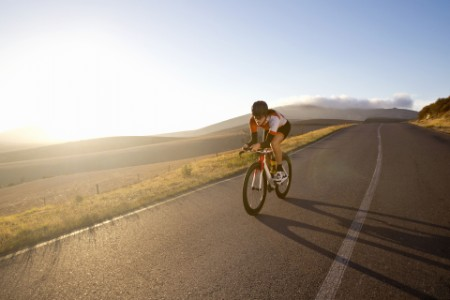 Female cyclist riding race bicycle on sunny open road