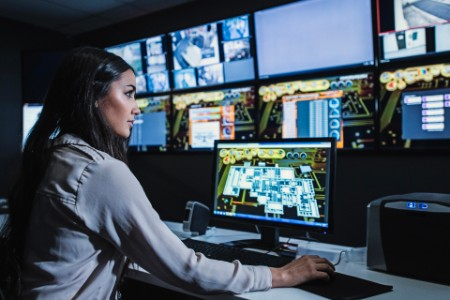 Female security guard watching monitors control room