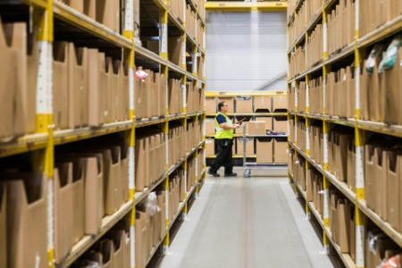 Female Warehouse Worker Pushes Cart