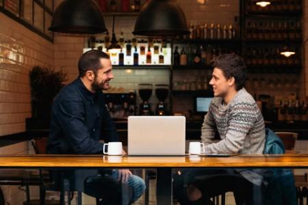 Amici che parlano al computer portatile in un caffè