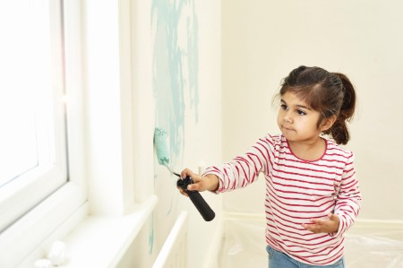 Girl painting walls roller