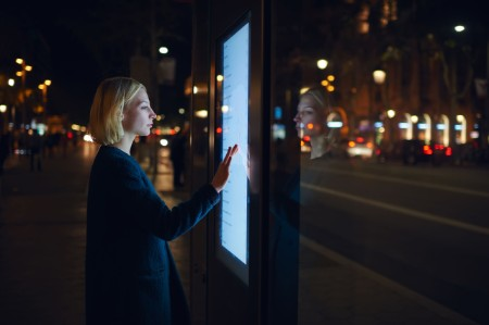 Girl using interactive map on city street at night