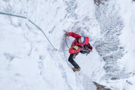 Alpinist pe perete de gheață iarna