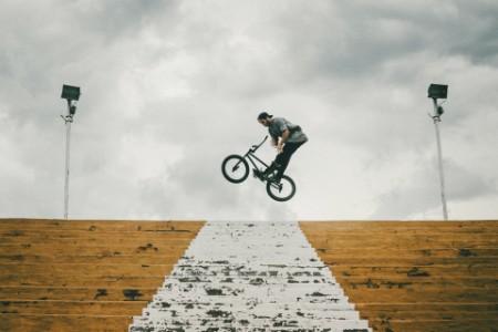 man performing bmx trick on steps
