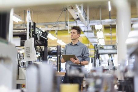 Man standing in factory with tablet looking sideways