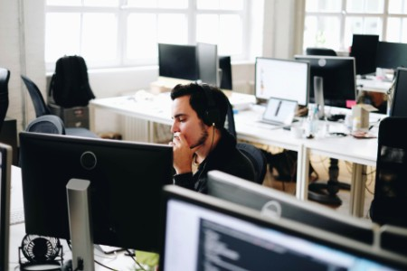 Man with headphones works alone in a modern office