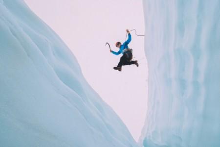 Man jumping over crevasse