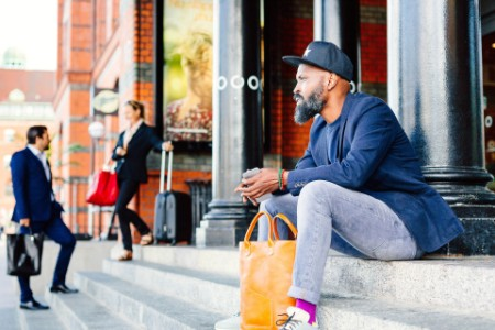 Businessman sitting on steps outside railroad station