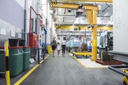 Three women walking in a factory shop