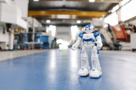 Toy robot standing on factory workshop