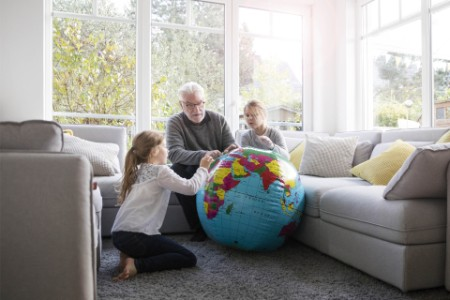 Two girls and grandfather with globe in living room