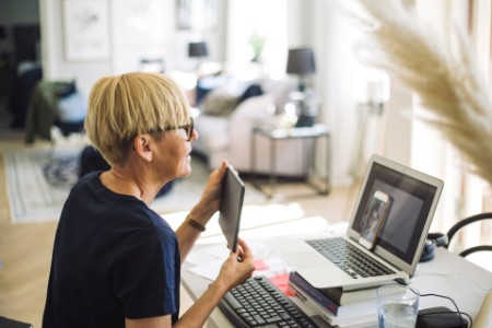 Woman showing tablet to friend on video call