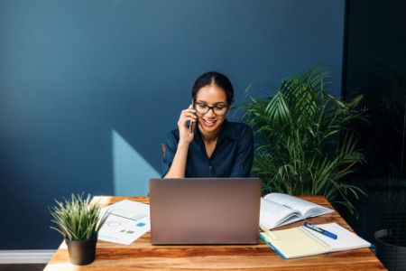 ey-woman-speaking-on-phone-at-desk