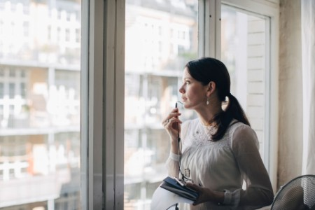 Woman talking on hands-free phone looking out of the window