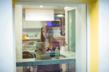 Woman using digital tablet while eating salad