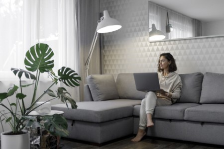 Woman with laptop sitting on couch