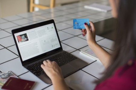 Young woman using laptop paying with credit card
