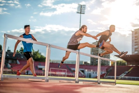 athletes jumping hurdles race stadium