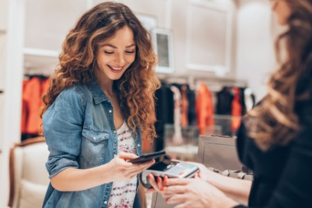 Woman making a smart phone payment in a fashion retail store