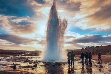 Multitud observando la erupción de un géiser