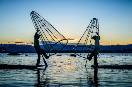 Two fishermen holding conical metal nets