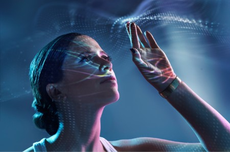 Woman reaching up to touch light rays