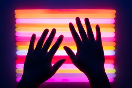 Hands in front of colorful neon lights