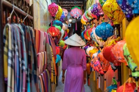 Mujer con ropa asiática caminando entre faroles chinos