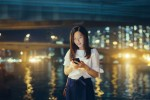Asian woman smartphone Hong Kong city skyline night