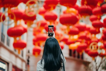 Asian woman taking picture of Chinese lanterns