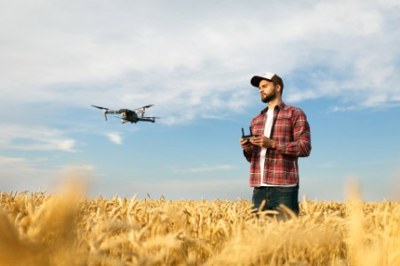 Compact drone hovers in front of farmer with remote controller in his hands