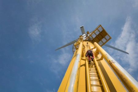 Engineer climbing ladder of wind turbine from boat at offshore windfarm