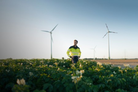 ey-engineer-standing-in-a-field-at-a-wind-farm