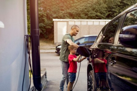 Father and son charging electric car outside home