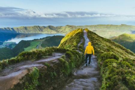 Человек в желтой куртке на смотровой площадке кратера вулкана на Азорских островах