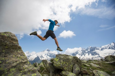 man leaping rock mountains