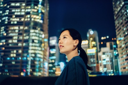 portrait of woman looking up to sky against city background