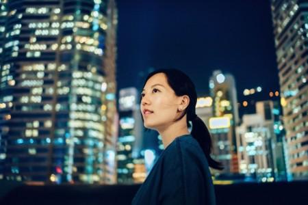 retrato de mujer mirando al cielo contra el fondo de la ciudad