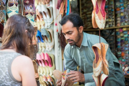 Salesman selling a shoe to a tourist